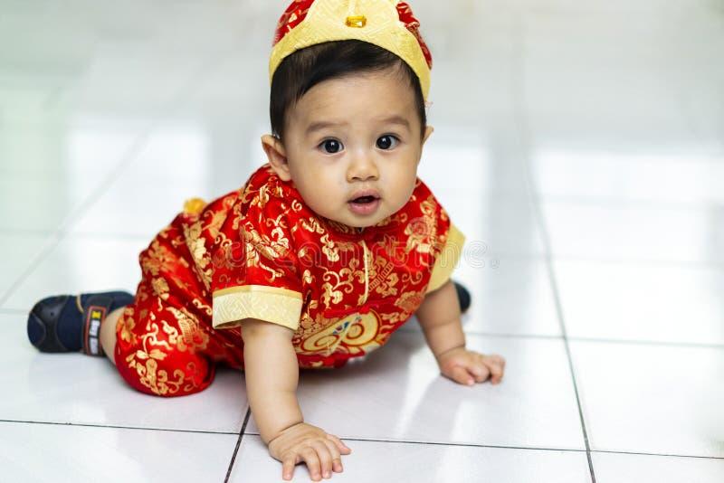 Asiatet behandla som ett barn genom att använda cheongsamklänningen för kinesiskt nytt år royaltyfria foton