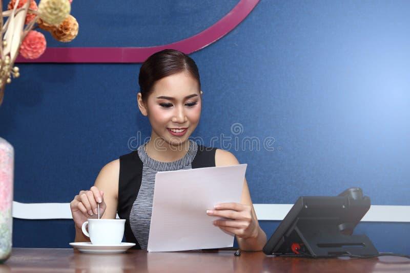 Asiatet för affärskvinnan har kaffe för arbete i morgon royaltyfri foto