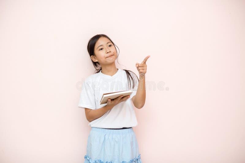 Asiatet garvade ståenden för hudflickabarnet över rosa väggbakgrund arkivbilder