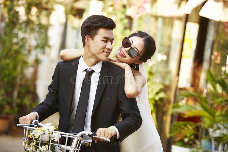 Asiatet gifta sig nyligen par som rider en cykel royaltyfri fotografi