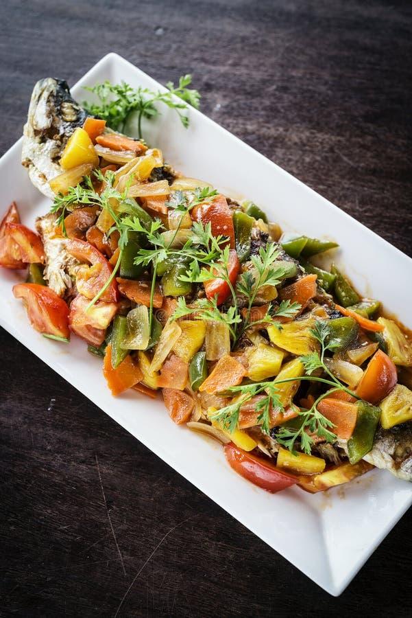 Asiatet grillade fisken med söta och sura grönsaker royaltyfria foton