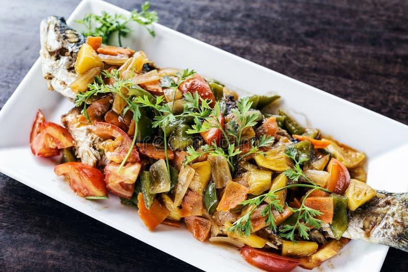 Asiatet grillade fisken med söta och sura grönsaker arkivfoto
