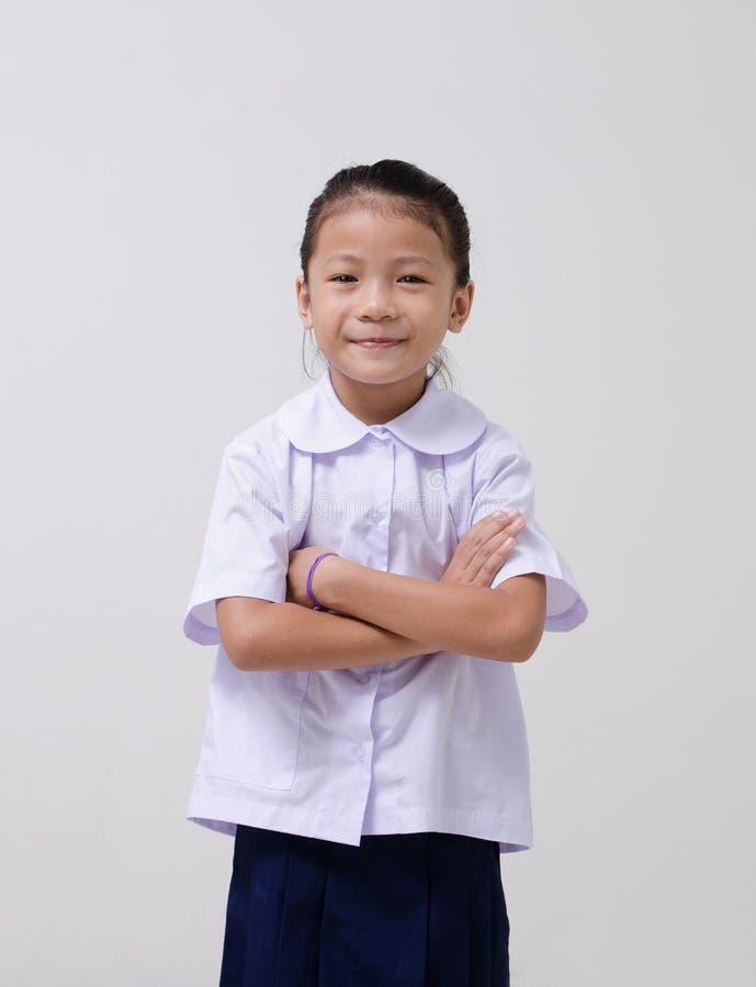 Asiatet lurar den gulliga flickan i studentens likformig på vit bakgrund arkivbilder
