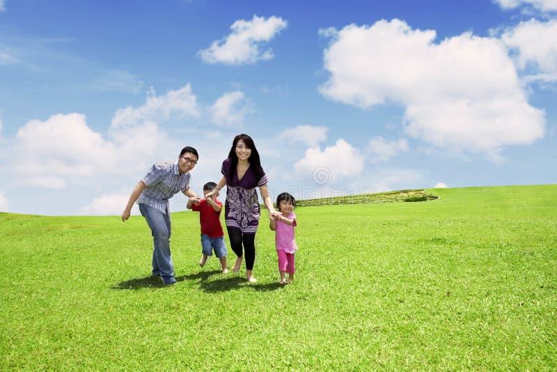 Asiatet uppfostrar att gå med deras barn i äng royaltyfria bilder