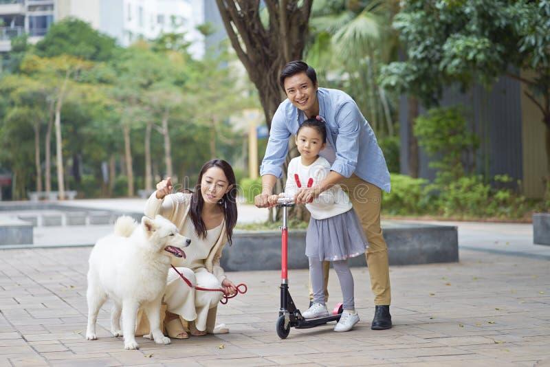 Asiatföräldrar & dotter som spelar sparkcykeln, medan gå hunden i trädgård royaltyfria foton