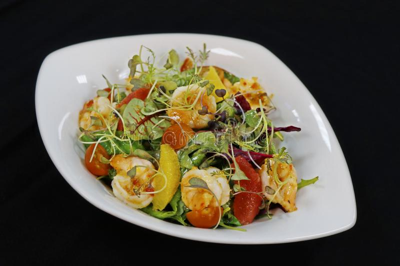 Asiatic style shrimps salad with citrus fruits and lettuce stock images