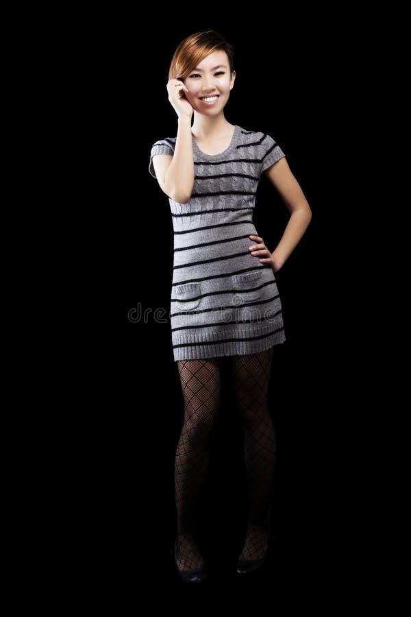 Asiatica Sorridente Donna Americana In Piedi Con Un Vestito Di Maglione Grigio fotografia stock