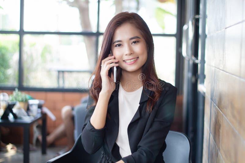 Asiatico della donna di affari che per mezzo del telefono per il celling e mandando un sms sul suo telefono cellulare fotografia stock libera da diritti