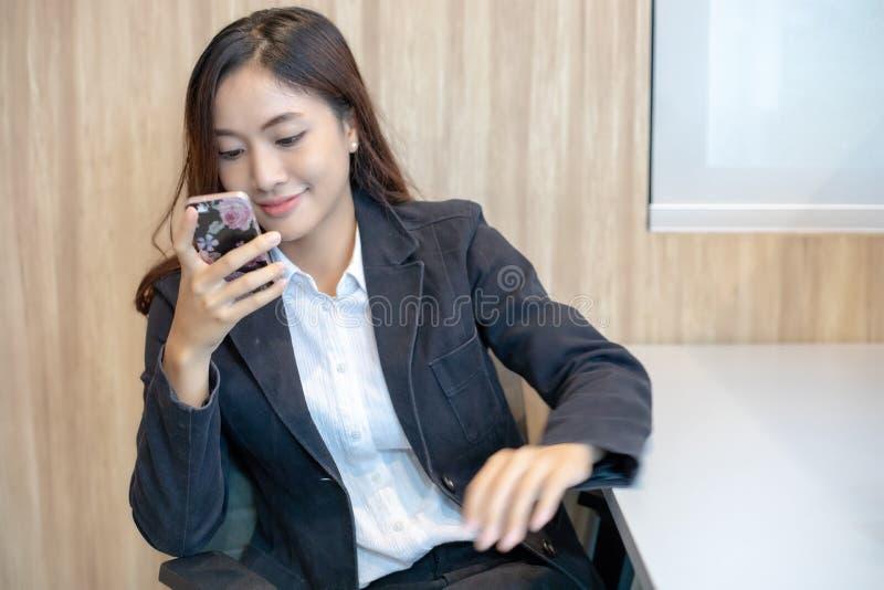 Asiatico della donna di affari che per mezzo del telefono per il celling e mandando un sms sulla sua m. immagini stock libere da diritti