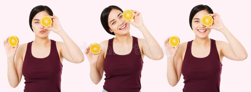 Asiatico felice stabilito, donna cinese con buona pelle che tiene le metà dell'arancia vicino al fronte, concetto dello skincare  immagini stock