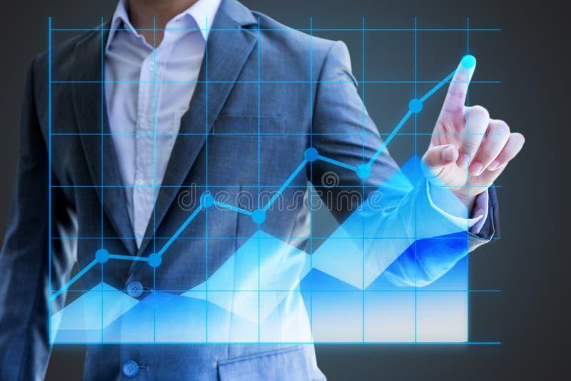 Asiatico statistica olografica di manifestazione della mano di uso dell'uomo d'affari del grafico lineare fotografia stock