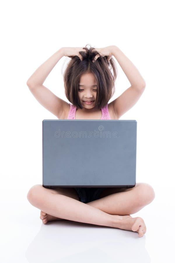 Asiatico sveglio che per mezzo del computer portatile e sconcertante immagine stock