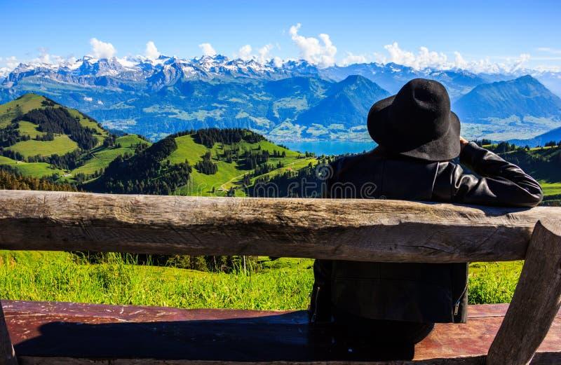 Asiatin auf der Bank hütet schönen szenischen Panoramablick von majestätischen Schweizer Alpen dieses umgebende Rigi Kulm lizenzfreies stockbild