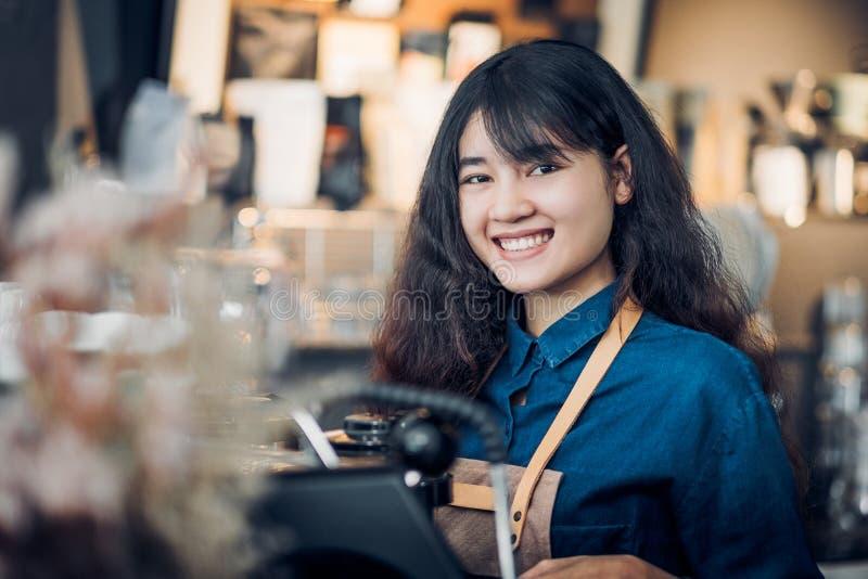 Asiatin barista, das heißen Kaffee mit Maschine an der Gegenbar und am Lächeln an der Kamera im Caférestaurant, in der Nahrung un stockfotografie