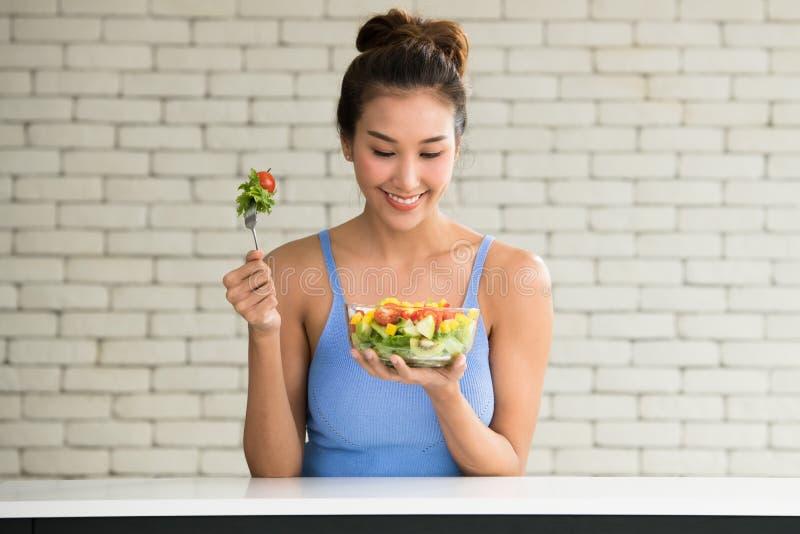 Asiatin in den frohen Lagen mit der Hand, die Salat hält stockfotos