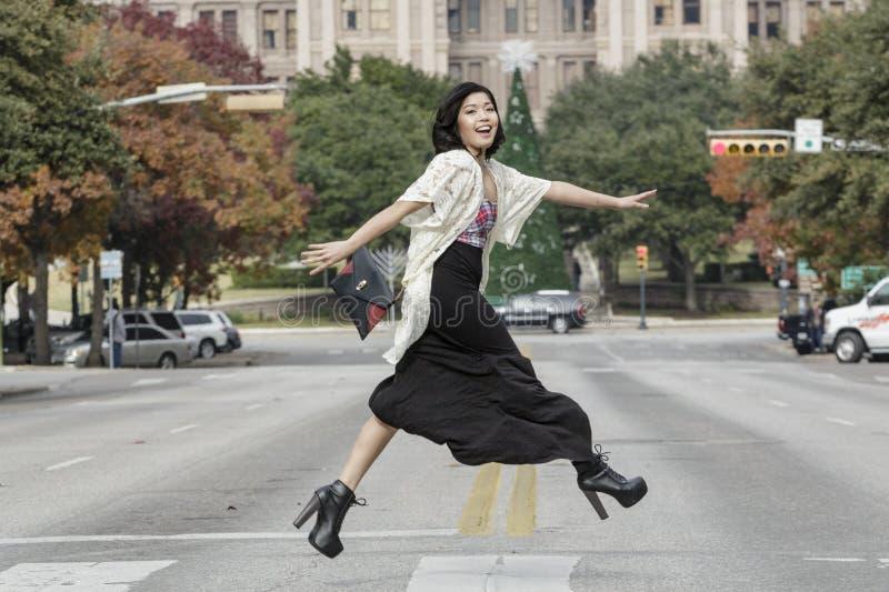 Asiatin in den Lebensstilstandorten, welche die Straßenstraße vor Hauptgebäude in Austin, Texas kreuzen lizenzfreies stockbild