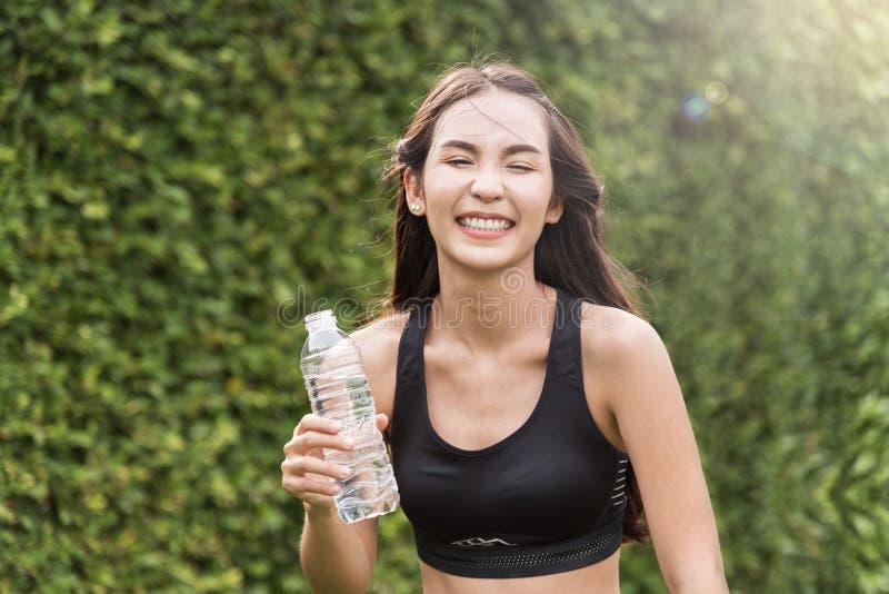 Asiatin in der Sportkleidung, die Flasche Wasser auf natürlichem BAC hält lizenzfreies stockbild
