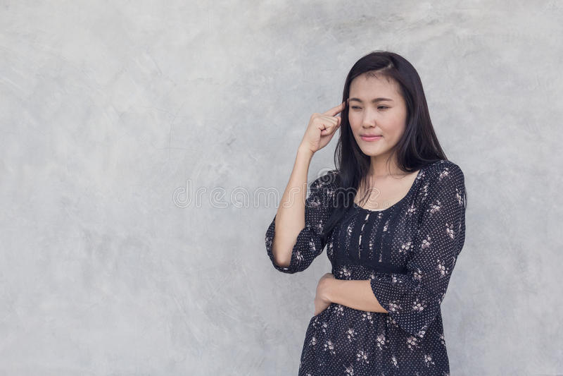 Asiatin, die auf Betonmauerhintergrund denkt lizenzfreie stockfotos