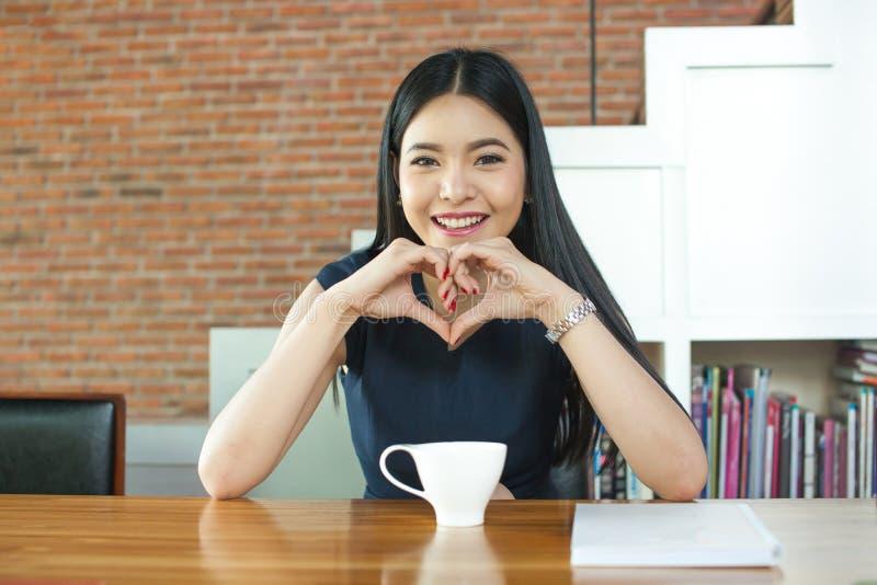 Asiatin, die auf dem Tisch vor Kaffee lächelt stockfoto