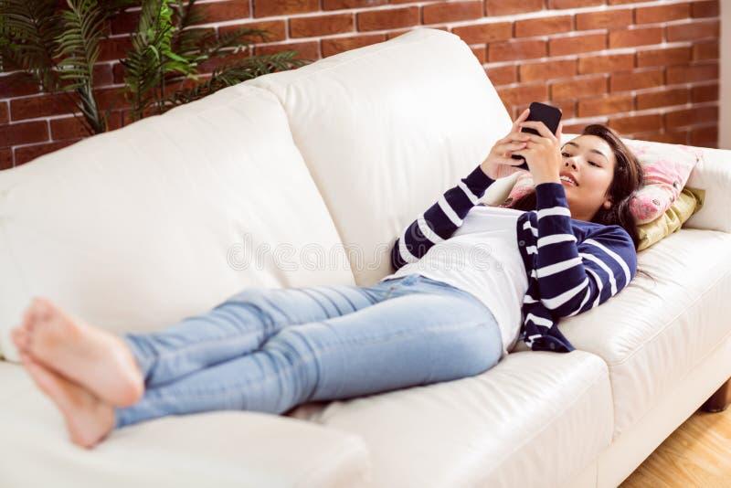 Asiatin, die auf der Couch unter Verwendung des Telefons liegt stockbilder