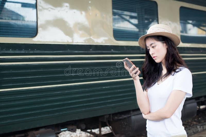 Asiatin, die auf Smartphone an der Bahnstation mit Eisenbahn simst stockfoto