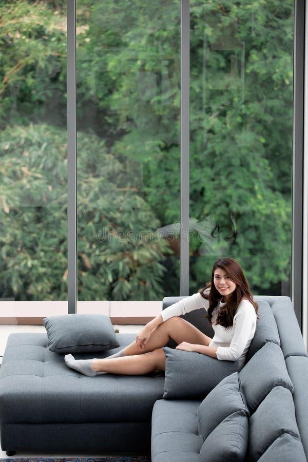 Asiatin, die auf Sofa nahe den großen Glasfenstern, allein entspannend im Haus mit grünem Wald im Hintergrund sitzt lizenzfreie stockbilder