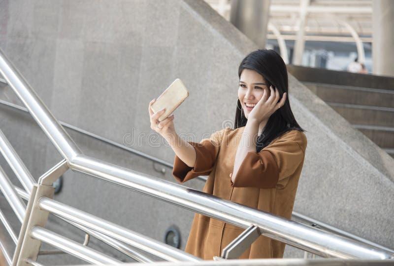 Asiatin, die das intelligente Telefon macht ein selfie Foto in der Stadt verwendet stockbild