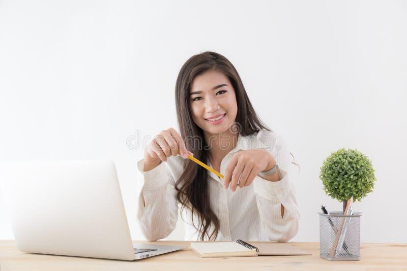 Asiatin, die in der Hand gelben Bleistift hält und Laptop, Femal verwendet stockbilder