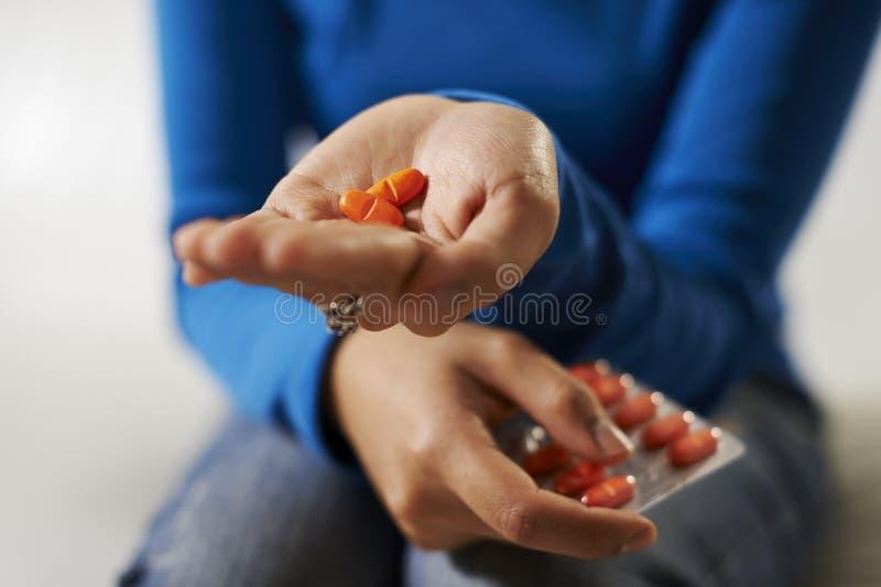 Asiatin, die in der Hand Pillen und Medizin hält stockfotografie