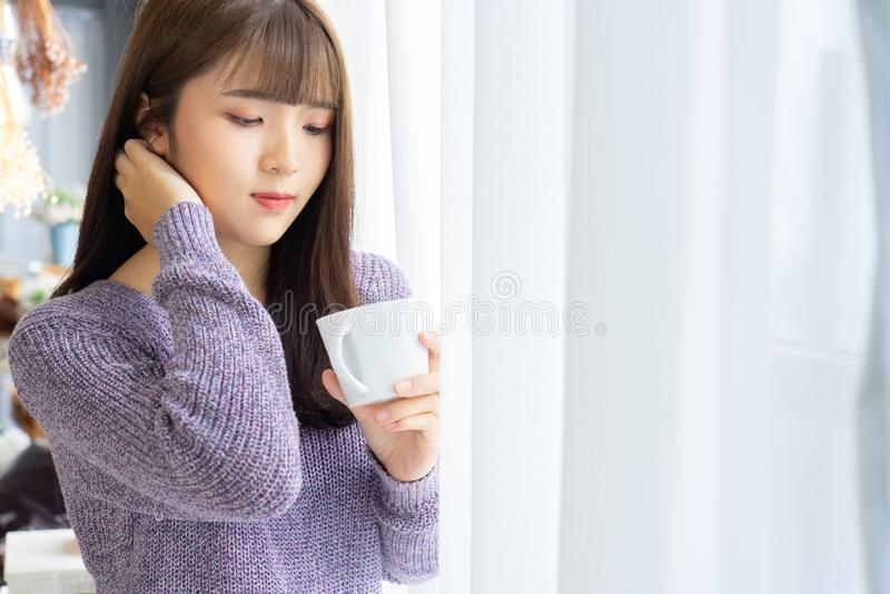 Asiatin, die einen Tasse Kaffee in ihren Händen auf dem hellen Ba hält stockbilder