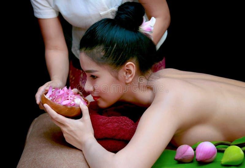 Asiatin, die Geruch von Blumen im Badekurortsalon hat lizenzfreie stockfotos