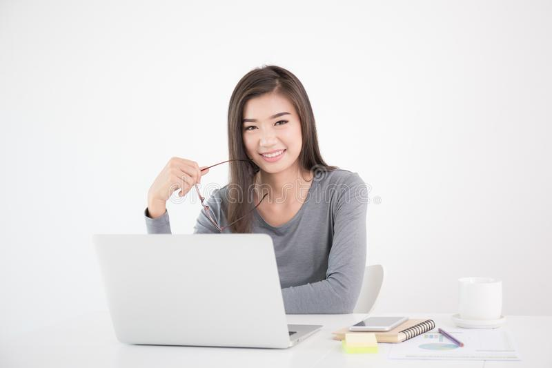 Asiatin, die Gläser in der Hand hält und Laptop, weibliches smil verwendet stockbilder