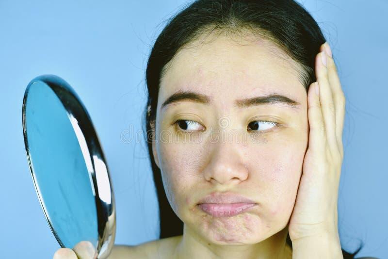 Asiatin, die ihr Gesichtsproblem im Spiegel, weibliches Gefühl betrachtet, über ihre Reflexionsauftrittshow die alternde Haut zu  stockfotos