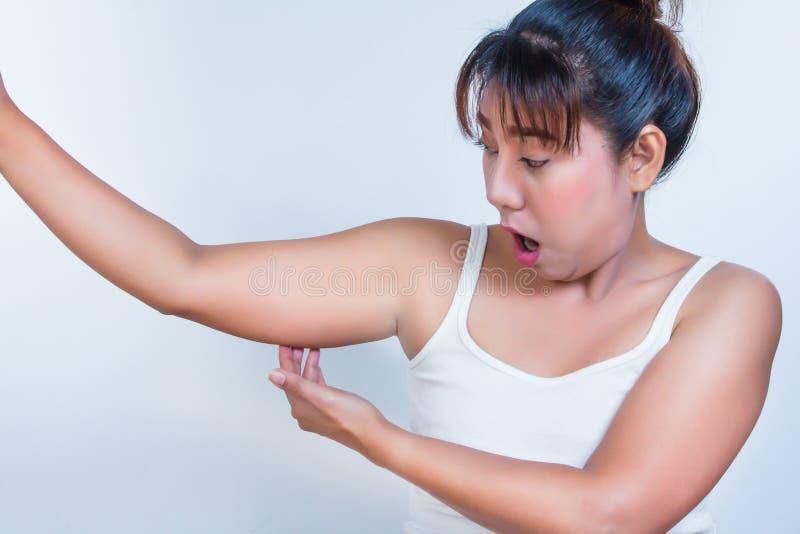 Asiatin, die ihren fetten Oberarm überprüft und lizenzfreie stockfotografie