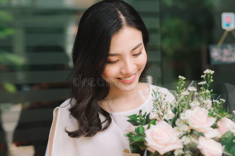 Asiatin, die im Blumenladen steht und Blumenstrauß von flowe hält stockfoto