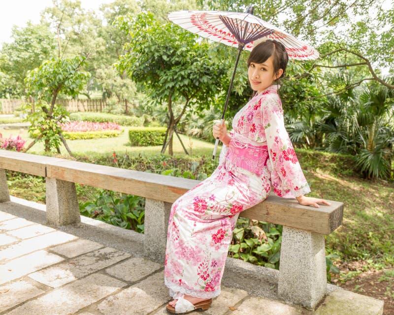Asiatin, die im Garten der japanischen Art sitzt lizenzfreies stockbild