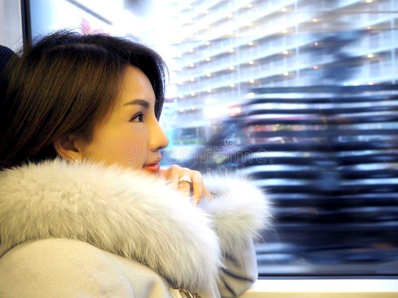 Asiatin, die innerhalb eines Zugs zum Stadtzentrum reist stockbilder