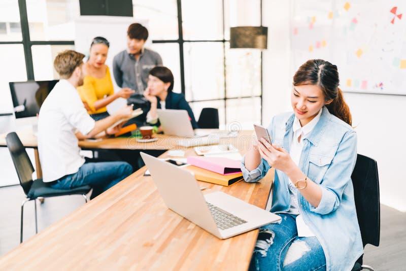 Asiatin, die intelligente Telefon-APP-Kontroll-E-Mail verwenden oder Textnachricht, multiethnisches verschiedenes Team, das im Hi lizenzfreie stockfotos