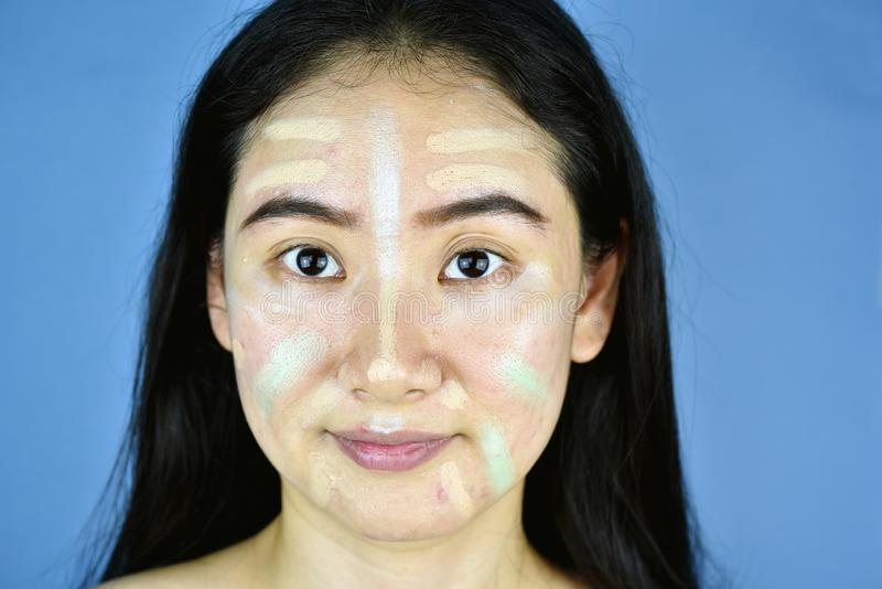 Asiatin, die Kosmetikmake-up anwendet und Farbkorrekturabdeckstift verwendet lizenzfreies stockfoto