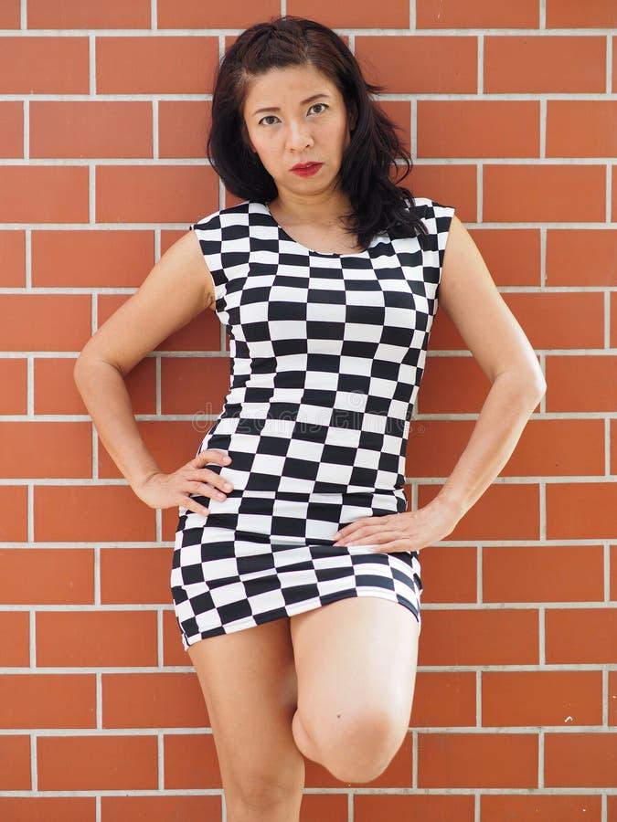 Asiatin, die kurzes kariertes Kleid trägt lizenzfreie stockbilder