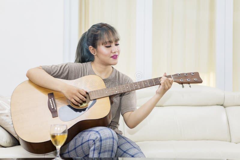 Asiatin, die lernt, eine Akustikgitarre zu spielen stockfotos