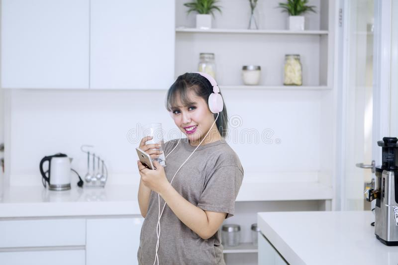 Asiatin, die Musik in der Küche genießt lizenzfreie stockbilder