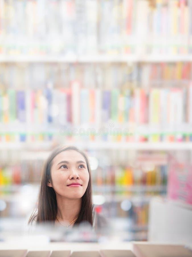 Asiatin, die nach Buch in unscharfem Bibliothekshintergrund sucht stockfotografie