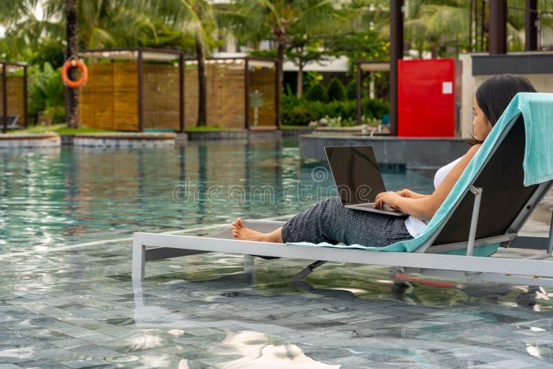 Asiatin, die am netten Swimmingpool sitzt und Laptop verwendet stockfotos