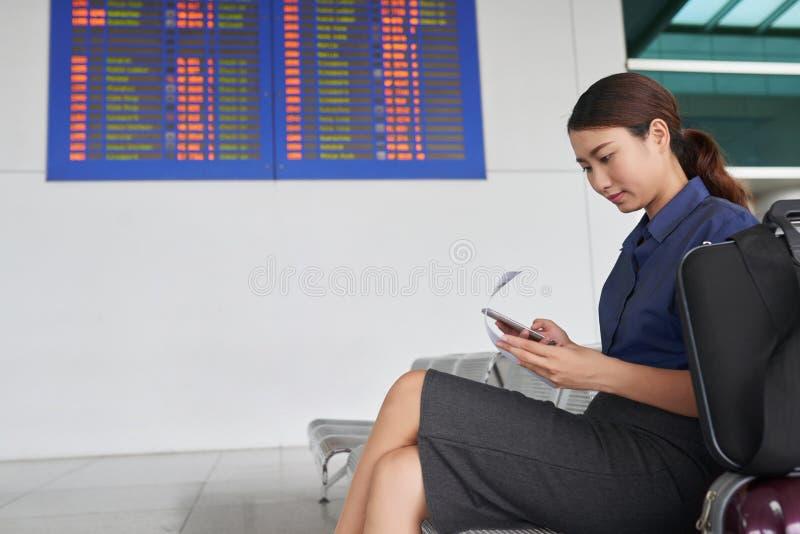Asiatin, die Smartphone im Flughafen verwendet stockfotografie