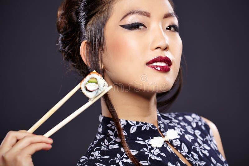 Asiatin, die Sushi isst, lizenzfreie stockfotografie