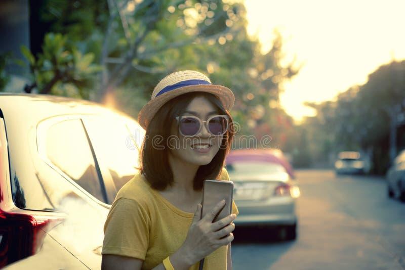 Asiatin durch Reisendlebensstil mit toothy lächelndem Entspannungsgefühl des Gesichtes des Smartphone in der Hand im citylife lizenzfreie stockfotografie