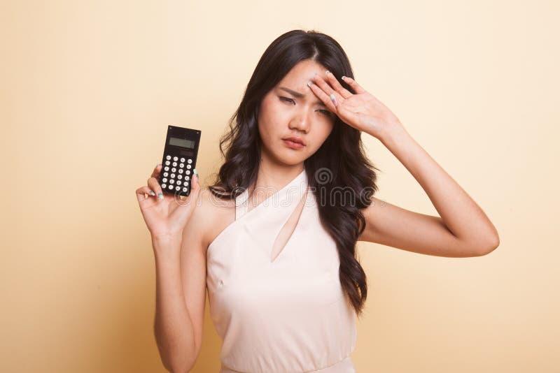 Asiatin erhielt Kopfschmerzen mit Taschenrechner stockfoto
