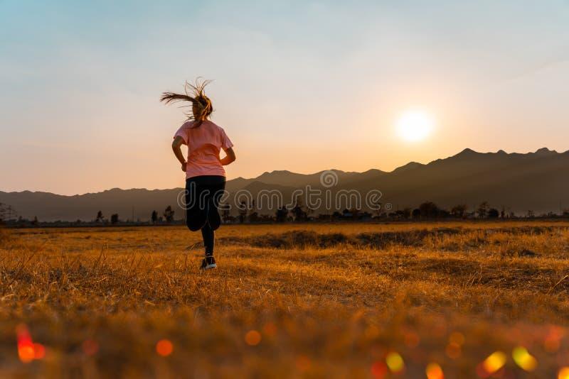 Asiatin genießen, mit schönem Sommerabend in der Landschaft draußen zu laufen lizenzfreies stockfoto