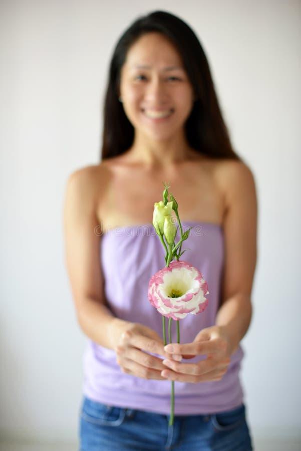 Asiatin im Hintergrund, der eine Blume hält stockfotos